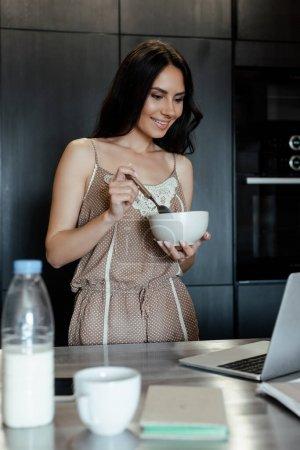Photo pour La femme souriante regardant l'ordinateur portable et tenant un bol pendant le petit déjeuner dans la cuisine, focalisation sélective - image libre de droit