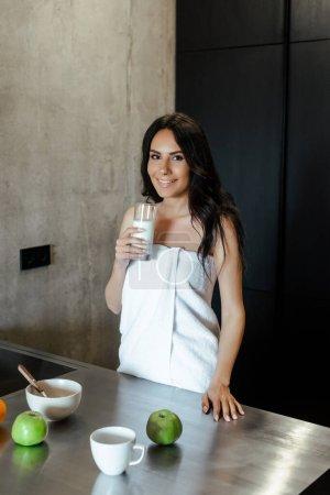 Photo pour Belle femme en serviette tenant un verre de vison et faisant le petit déjeuner sur la cuisine le matin - image libre de droit