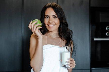 Photo pour Une femme souriante dans une serviette tenant une pomme et un verre de vison dans la cuisine le matin - image libre de droit