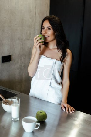 happy woman in towel eating apple for breakfast on kitchen in morning