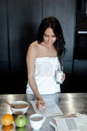 Photo pour Attractive woman in towel doing paperwork during breakfast on kitchen in morning - image libre de droit