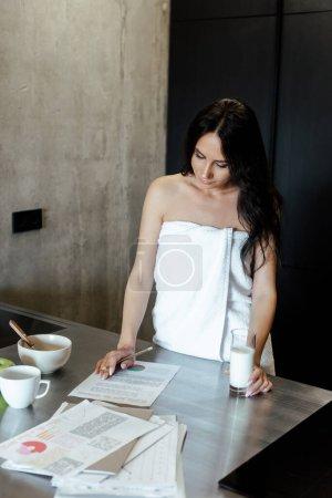 Photo pour Belle femme en serviette faisant de la paperasserie au petit déjeuner le matin dans la cuisine - image libre de droit