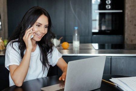 Photo pour Femme heureuse parlant sur smartphone et travaillant avec un ordinateur portable sur la cuisine pendant l'isolement personnel - image libre de droit