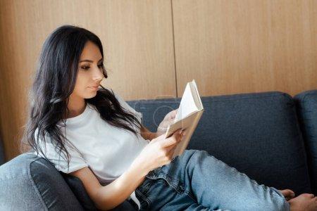 Photo pour Belle jeune femme lecture livre sur canapé à la maison - image libre de droit