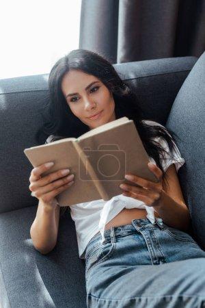 Photo pour Belle fille positive livre de lecture sur canapé dans le salon - image libre de droit