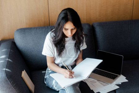 beautiful girl working with business documents on sofa with laptop during self isolation