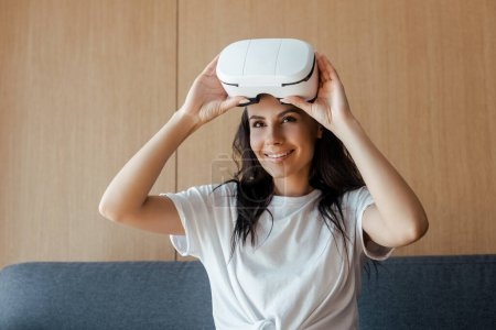 Photo for Attractive smiling woman in virtual reality headset at home - Royalty Free Image