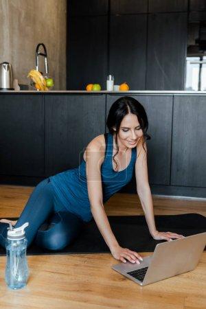 Photo pour Sourire belle sportive assise sur tapis de fitness avec bouteille d'eau et ordinateur portable - image libre de droit