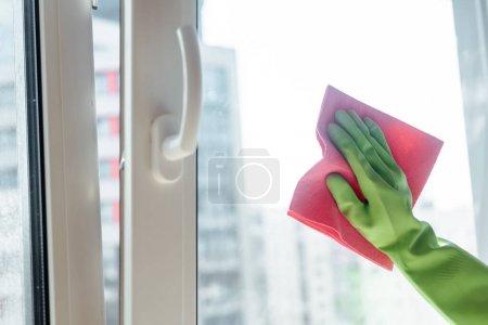 Teilansicht eines Mädchens im Gummihandschuh, das Fenstergriff mit rosa Lappen putzt