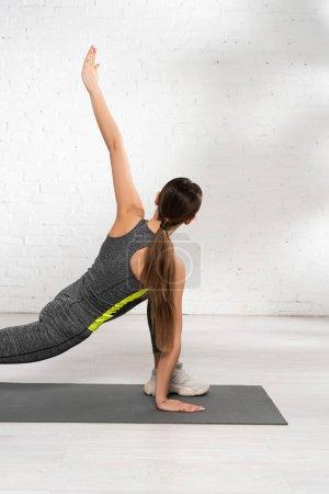 Photo pour Vue arrière de la femme sportive avec la main tendue s'exerçant sur le tapis de fitness - image libre de droit