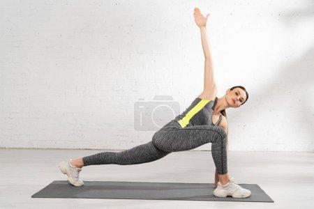Photo pour Attrayant sportif avec la main tendue exercice sur tapis de fitness - image libre de droit