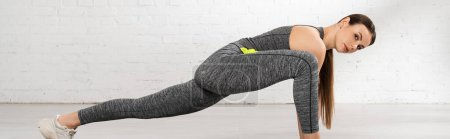 panoramic shot of young and attractive sportswoman stretching and looking at camera
