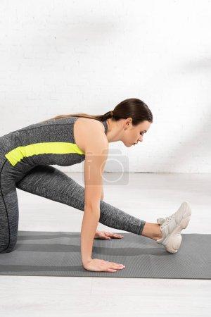 Photo pour Profil de la jeune femme flexible étirant sur tapis de fitness dans le centre sportif - image libre de droit