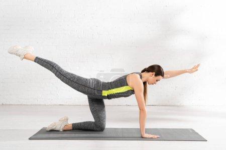 Photo pour Profil de sportive concentrée avec main tendue travaillant sur tapis de fitness - image libre de droit