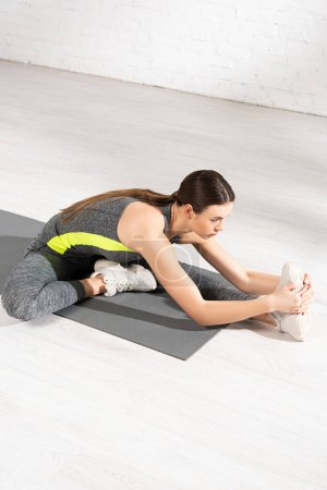 young and attractive sportswoman warming up on fitness mat