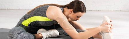 Photo pour Orientation panoramique de la jeune et attrayante sportive échauffement sur tapis de fitness - image libre de droit