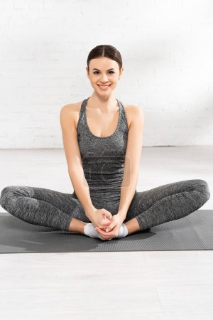 happy sportswoman stretching on fitness mat and looking at camera