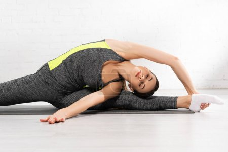 flexible and sportive girl with closed eyes stretching on fitness mat