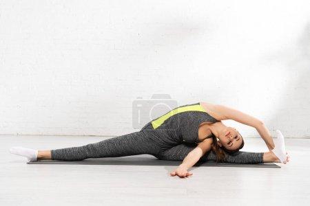 Photo pour Jeune femme flexible étirant sur tapis de fitness - image libre de droit