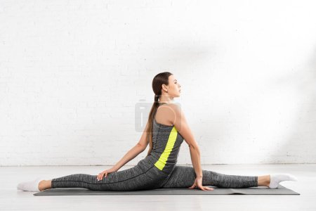 Photo for Side view of flexible and sportive girl doing twine on fitness mat - Royalty Free Image