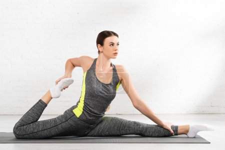 Photo for Flexible and sportive woman doing twine and stretching on fitness mat - Royalty Free Image