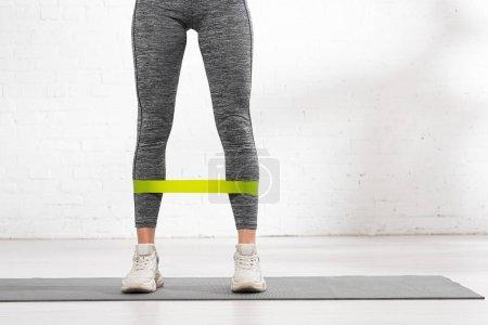 Photo pour Vue recadrée de fille sportive avec bande de résistance debout sur tapis de fitness - image libre de droit
