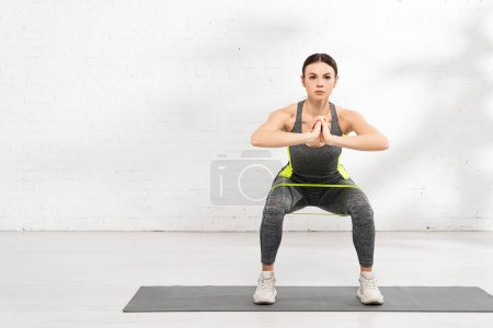 Photo for Athletic girl with praying hands exercising with resistance band on fitness mat - Royalty Free Image