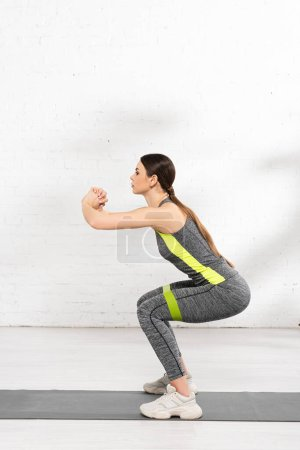 Photo pour Vue latérale de la fille athlétique faisant squat tout en faisant de l'exercice avec bande de résistance sur tapis de fitness - image libre de droit