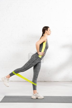 Photo for Sportive girl with hand on hip exercising with resistance band on fitness mat - Royalty Free Image