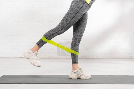 Photo for Cropped view of woman exercising with resistance band on fitness mat - Royalty Free Image