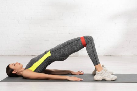Photo for Side view of sportive woman with working out with resistance band on fitness mat - Royalty Free Image