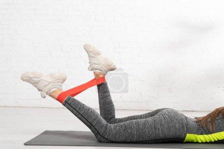 Photo pour Vue recadrée de la femme sportive allongée sur un tapis de fitness et s'entraînant avec une bande de résistance - image libre de droit