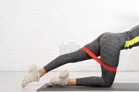 cropped view of sportive woman standing on knee and working out with resistance band