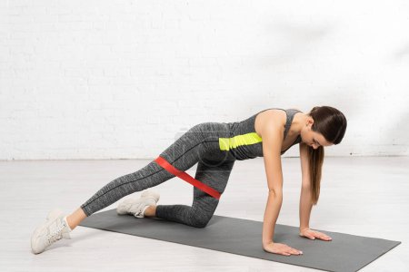 Photo for Sportive woman standing on knee on fitness mat and working out with resistance band - Royalty Free Image