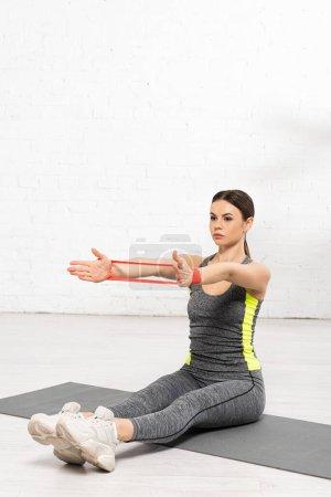 Photo pour Femme sportive assis sur tapis de fitness et de l'exercice avec bande de résistance - image libre de droit
