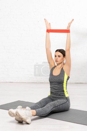 Photo pour Sportive avec les mains tendues, assise sur un tapis de fitness et s'entraînant avec une bande de résistance - image libre de droit