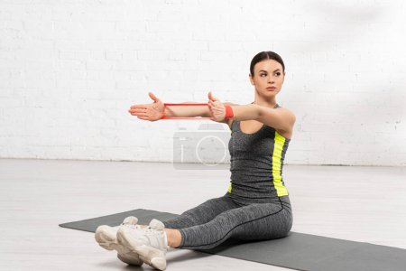 sportive girl with outstretched hands sitting on fitness mat and working out with resistance band