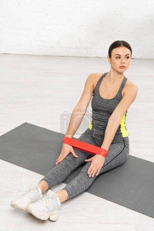 Photo pour Sportswoman assise sur un tapis de conditionnement physique et s'entraînant avec une bande de résistance - image libre de droit