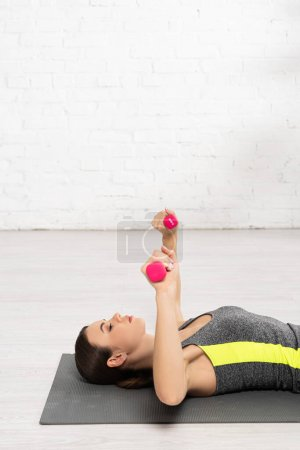 Photo for Side view of young sportswoman exercising with dumbbells and lying on fitness mat - Royalty Free Image