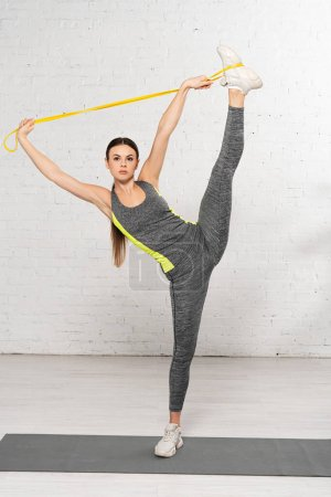 Photo for Sportswoman holding resistance band above head while exercising on fitness mat - Royalty Free Image
