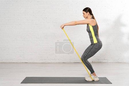 Photo pour Vue latérale de la femme en tenue de sport travaillant avec une bande de résistance sur un tapis de fitness près d'un mur de briques blanches - image libre de droit