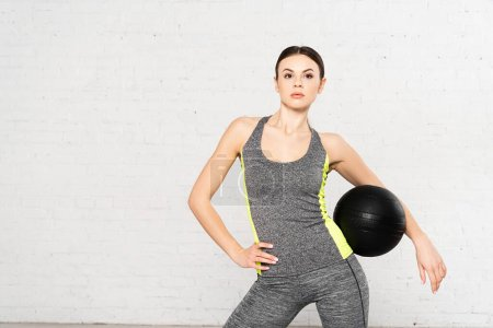 attractive woman in sportswear standing with black ball and hand on hip