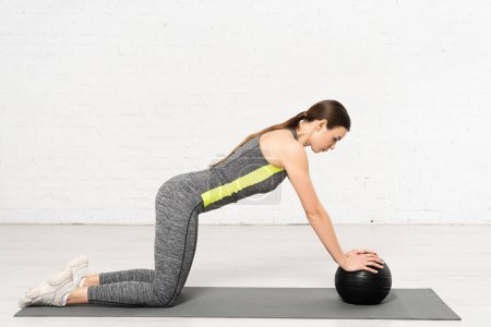 Photo for Side view of attractive girl in sportswear exercising with black ball on fitness mat - Royalty Free Image