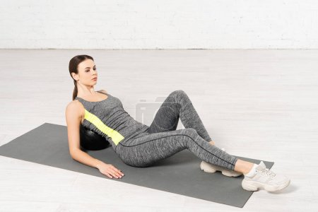 sportswoman in sportswear lying on ball while exercising on fitness mat