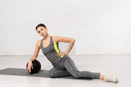 Photo pour Sportive en vêtements de sport avec la main sur la hanche toucher boule noire - image libre de droit