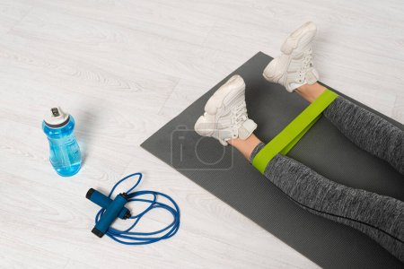 Photo for Cropped view of woman working out with resistance band near skipping rope and sports bottle - Royalty Free Image