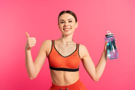 happy sportswoman showing thumb up and holding sports bottle with water isolated on pink