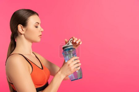 Photo for Side view of sportswoman holding sports bottle with water isolated on pink - Royalty Free Image