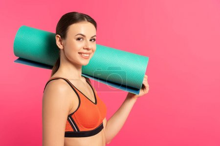 Photo pour Heureuse sportive tenant tapis de fitness isolé sur rose - image libre de droit