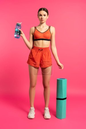 Photo for Attractive sportswoman holding sports bottle with water and standing near fitness mat on pink - Royalty Free Image